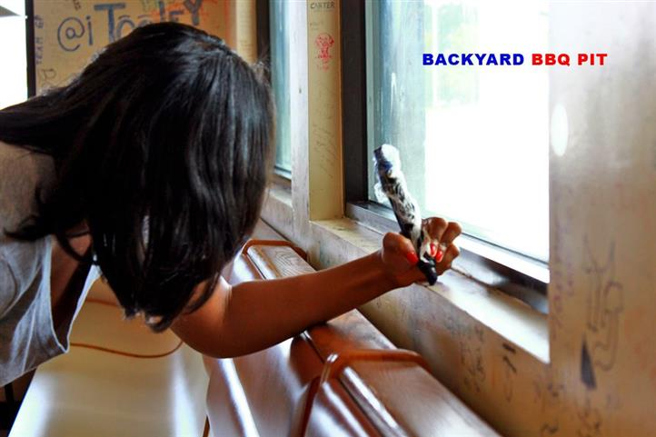 woman drawing on the walls of backyard bbq pit