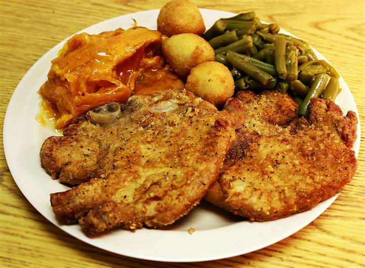 fried fish entree with vegetables and hush puppies