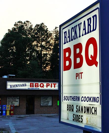outside signage of backyard bbq pit in front of the establishment