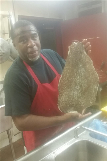 chef holding up a large fillet of fish