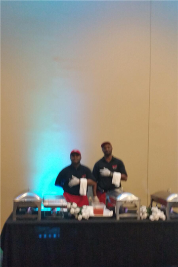 two chefs standing behind a catering style table with metal trays