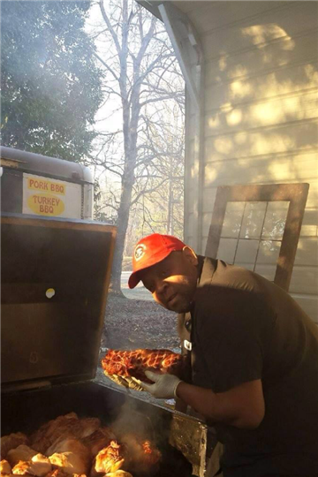 pitmaster putting meat on the smoker outside