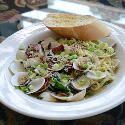 Spaghetti with clams, bacon, spinach, scallions and italian bread slice on white dish.