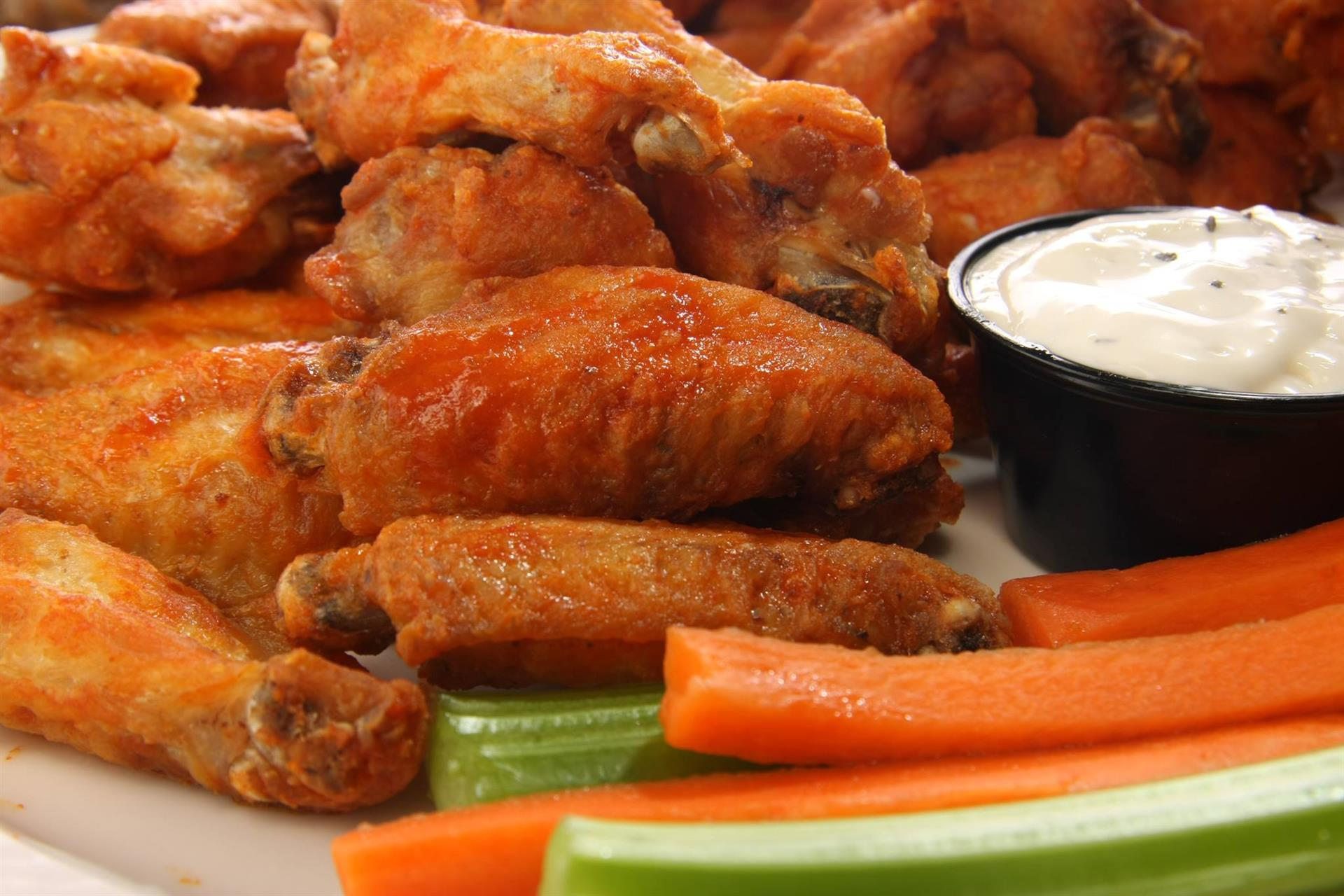 Assortment of buffalo wings with celery and carrots with dipping sauce