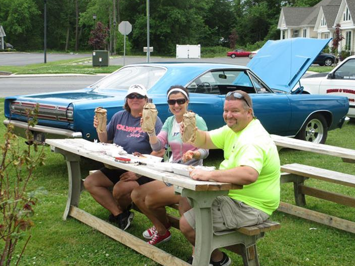 people sitting at  picnic table eating bbq
