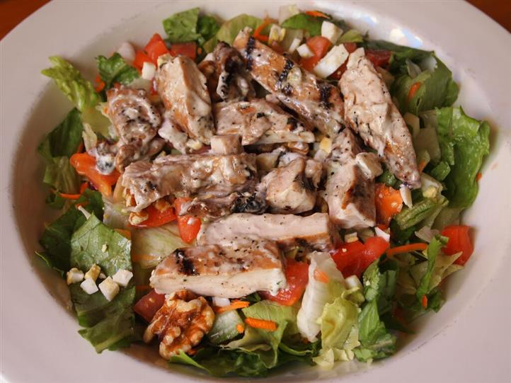 salad with lettuce, tomatoes, cheese, grilled chicken and walnuts