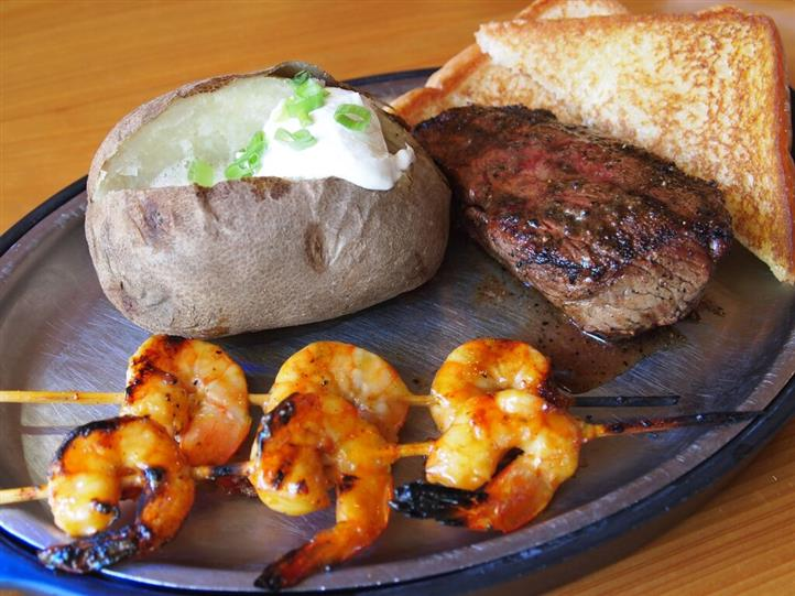 steak with shrimp skewers and a baked potato
