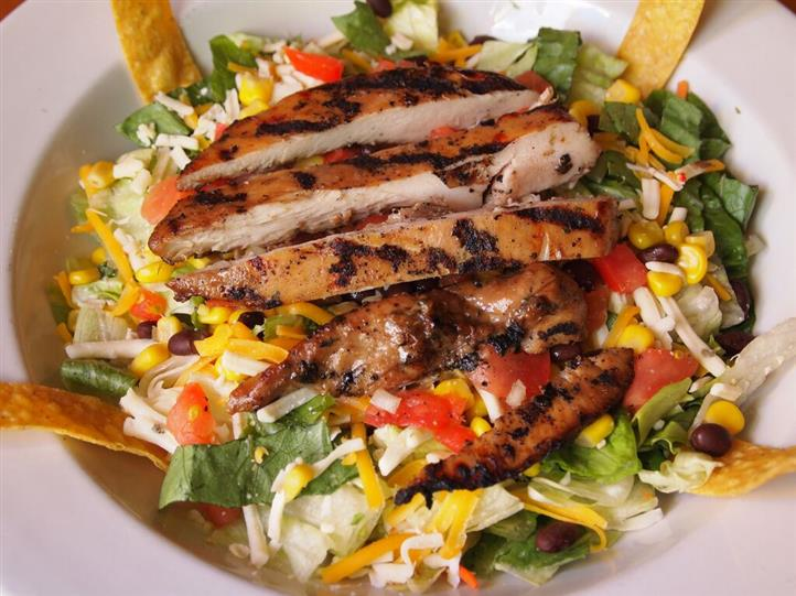 salad with lettuce, tomatoes, beans, cheese and grilled chicken