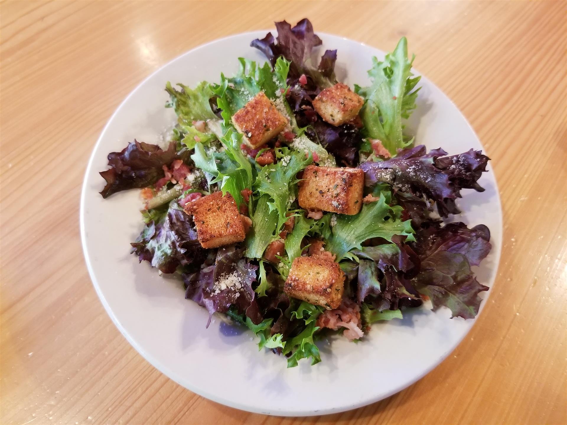 rustic Caesar salad is A unique blend of European small leaf lettuces, with the traditional toppings of Parmesan Cheese, Bacon Bits, and Homemade Croutons, make this Caesar Salad truly unique!