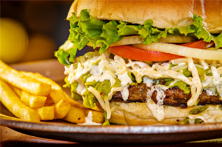 burger with avocado, coleslaw, lettuce, tomato and lettuce with fries on the side