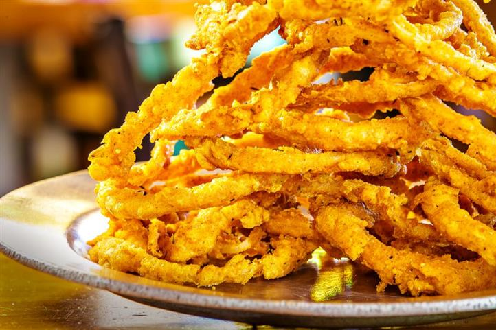 deep fried onion rings stacked together on a plate