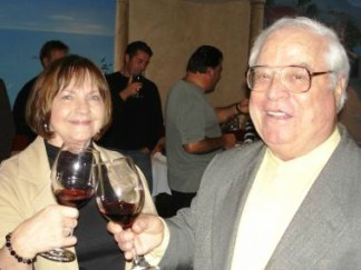 male and female holding glasses of wine