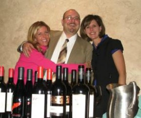male and two females posing for picture behind bottles of wine