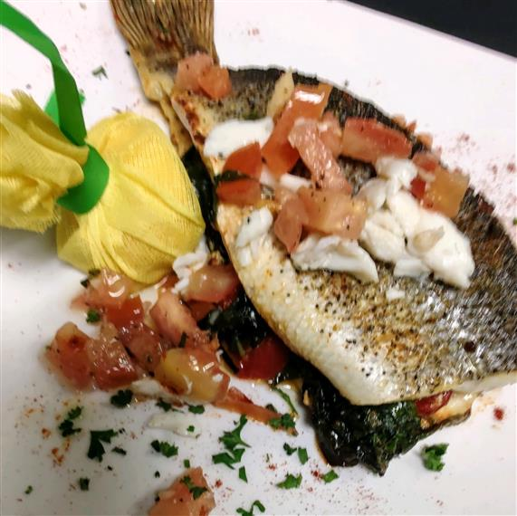 Branzino stuffed with spinach and roasted red peppers oven roasted topped with a crab tomato amolio