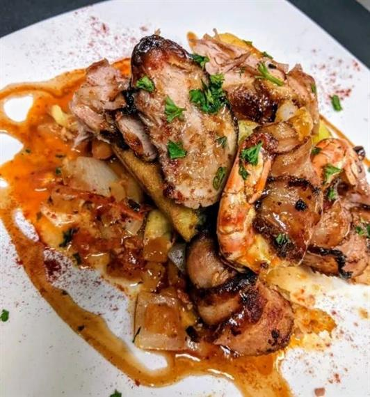 Jalapeno bacon wrapped jumbo shrimp served over rice topped with pulled pork and creole sauce finished with maple bbq.