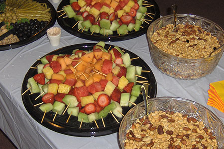 Fruit with toothpicks, bowls of nuts, tray of olives on catering table