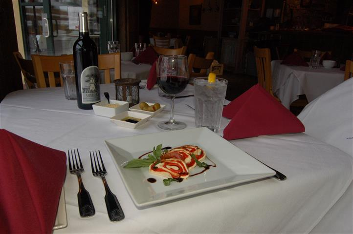entree on a plate with two forks, a knife and a glass of water