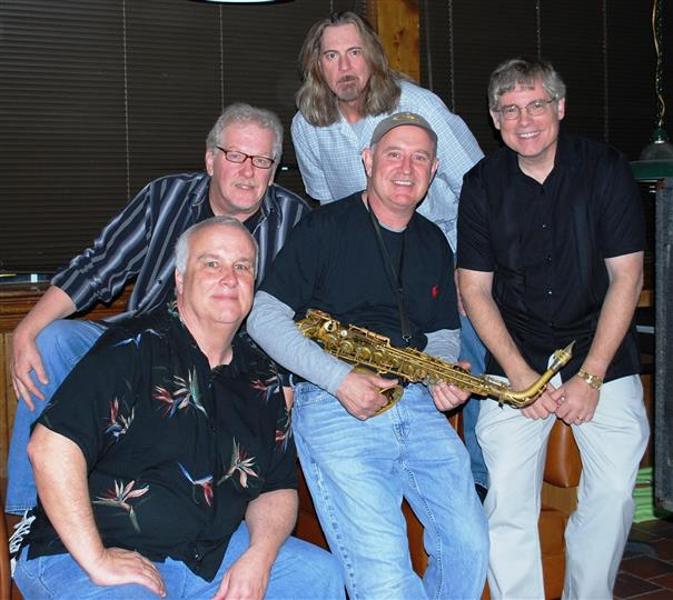 5 men, one is holding a saxophone