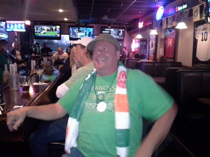 happy man with irish-themed shirt and towel