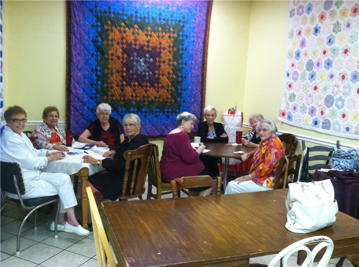 several women at tables, with quilts hung on the walls