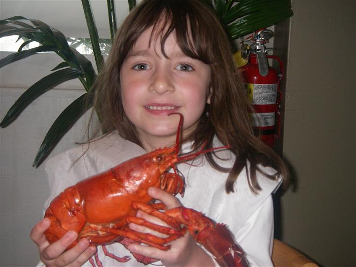 little girl holding a cooked lobster