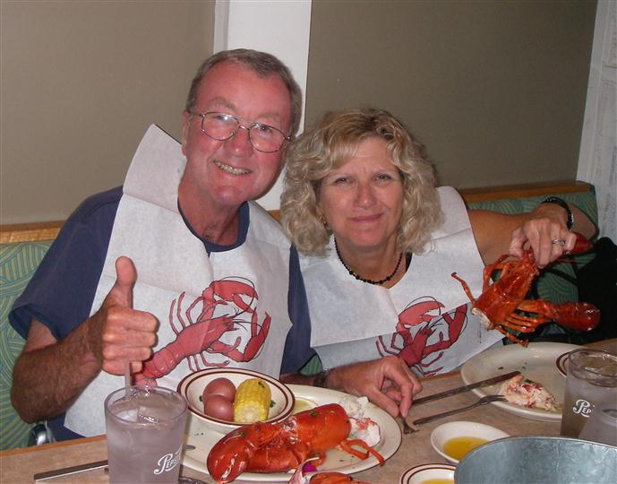 Couple smiling and holding their cooked lobsters up with bibs on