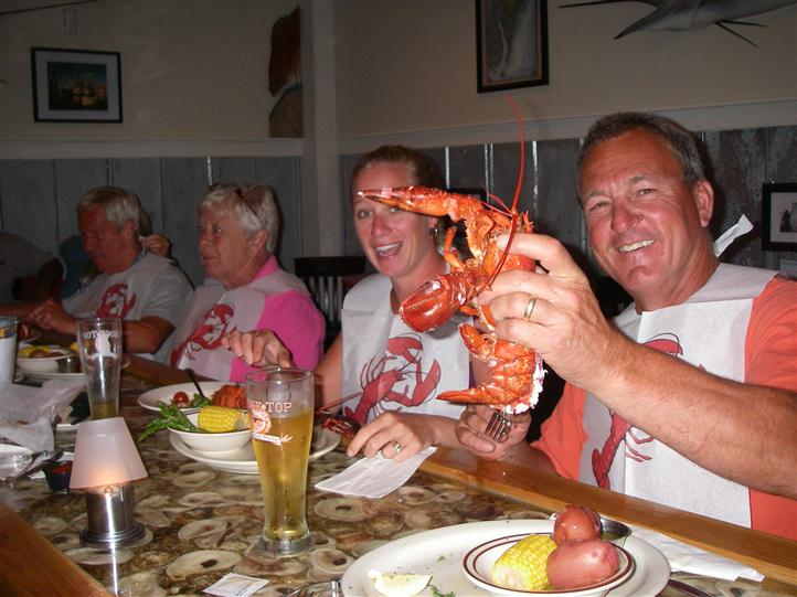 Family smiling and holding their cooked lobsters up with bibs on