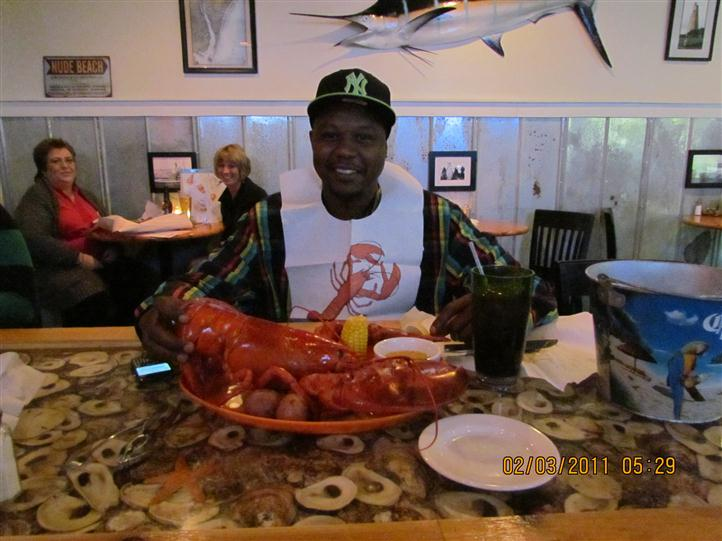 a man smiling in front of a huge lobster wearing a lobster bib