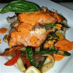 salmon menu item on a bed of grilled vegetables with orange sauce