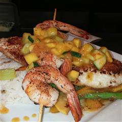 Menu item with grilled shrimp on a skewer and fried scallops