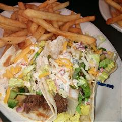 fish tacos with lettuce and cheese in a soft taco shell with a side of fries