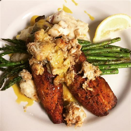 Lightly blackened Pompano resting on grilled asparagus and mashed potatoes, topped with crab meat, bay scallops and hollandaise sauce