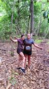 two girls smiling in the woods covering in mud