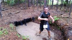 boy in a mud puddle competing mud run 2015 course