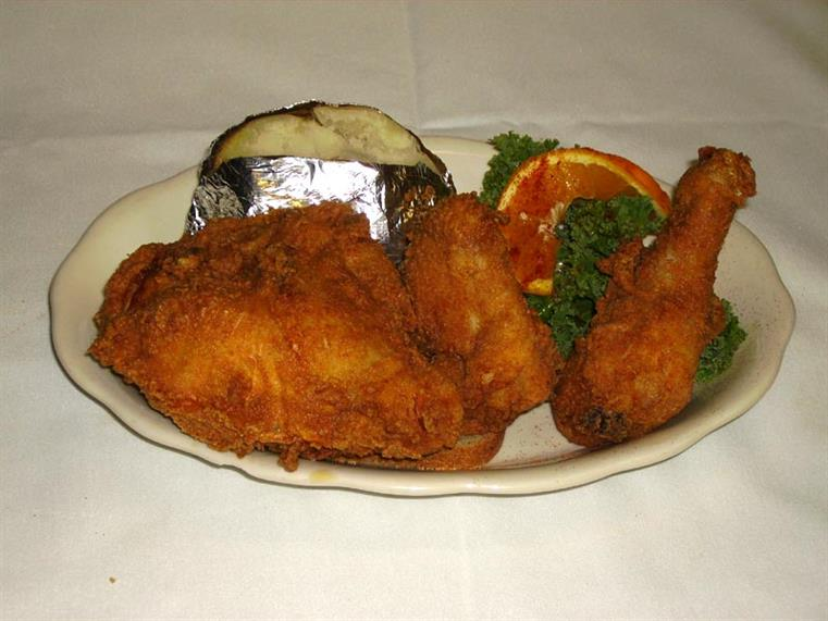 fried fish on a plate with a baked potato