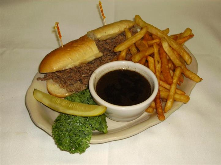 Prime rib sandwich with side of au jus, pickle, french fries