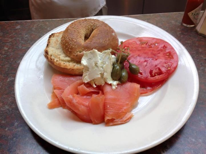 Bagel with cream cheese and olives, tomatoes, and ham
