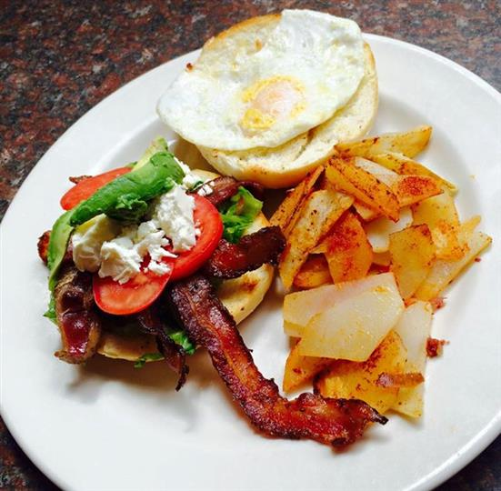 Bacon and egg sanwich with vegetables with a side of sliced potatoes