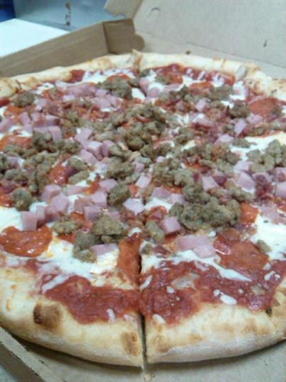 Pizza topped with bacon, and beef
