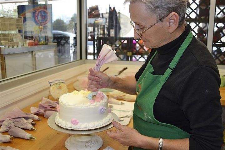 employee decorating a cake