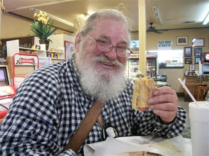 Man smiling with a sandwich