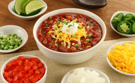 chili served in a bowl with sides of sauces, cheese, lime wedges and other