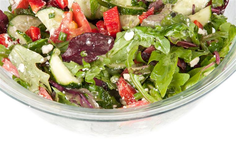 Salad with mixed greens, tomatoes, cucumbers, olives and dressing served in a bowl