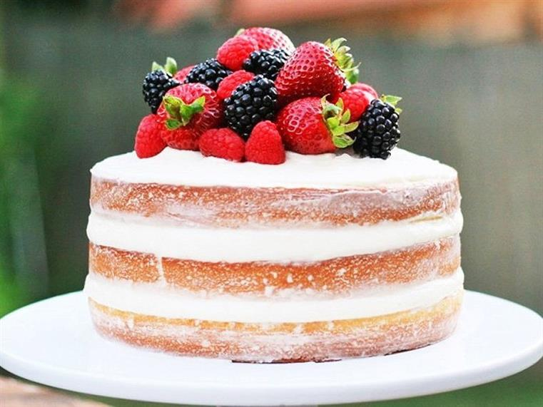 Multi-tier cake with icing and fresh fruits