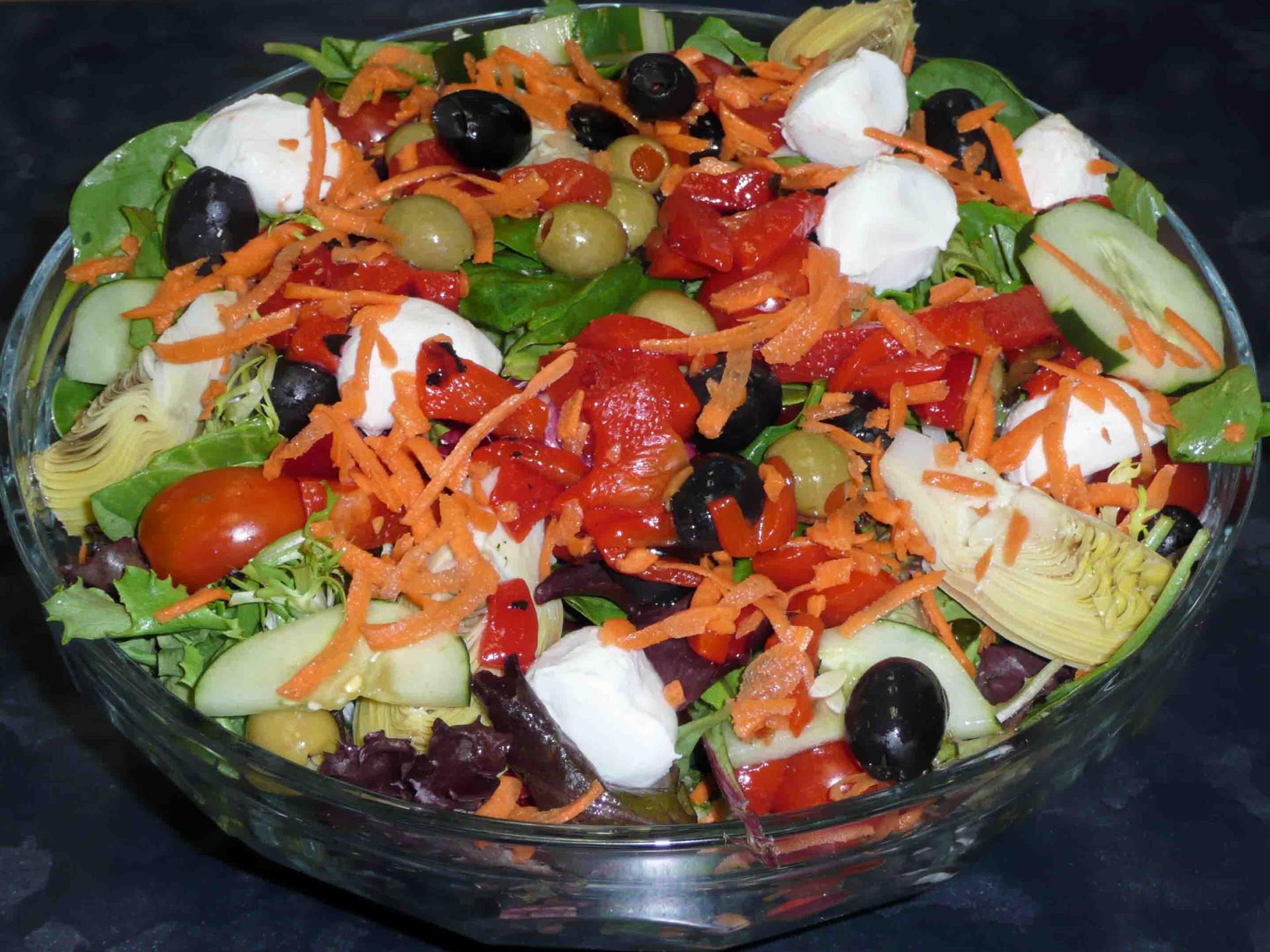 large salad with carrots, black and green olives, cucumbers and tomatoes