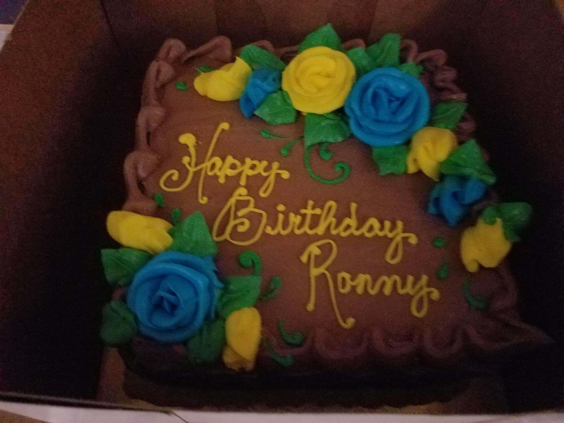 "Birthday cake for Ronny, stating ""Happy Birthday Ronny"". Chocolate icing with blue and yellow roses"