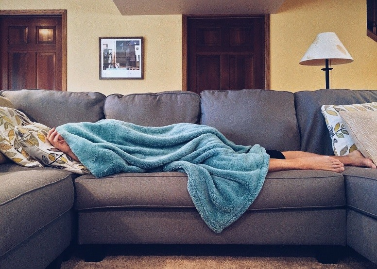 Person laying on the couch with a blanket covering them