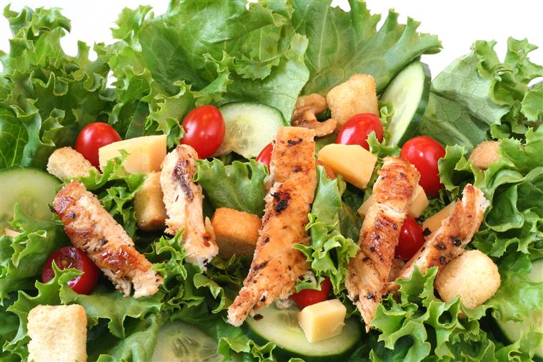 grilled chicken on a salad with croutons, cucumbers and tomatoes