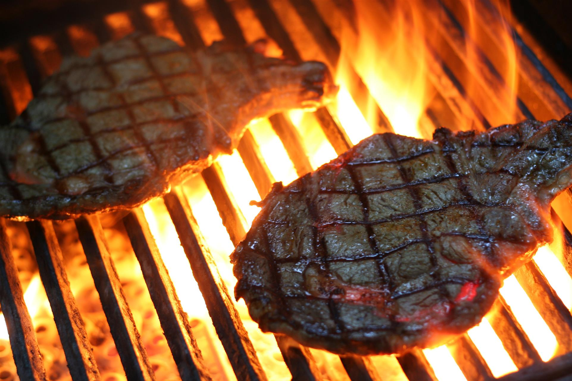 two steaks on a flaming grill