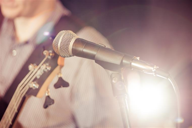closeup of a microphone with a guitar player in the background